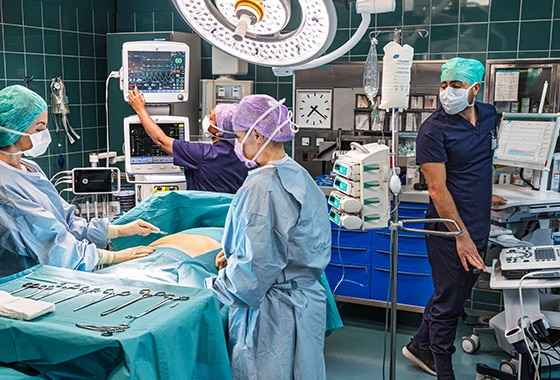 A caregiver sets up a GE Healthcare CARESCAPE B650 to monitor the patient's data during a surgery in hospital.