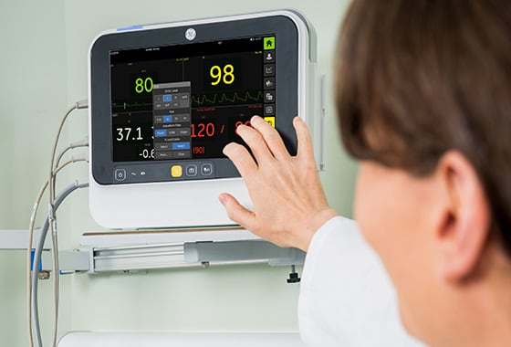 A caregiver uses touch screen of GE Healthcare B105 and B125 monitors to monitor patient data.