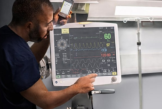 A male user is showing patient data via GE Healthcare patient monitoring systems.