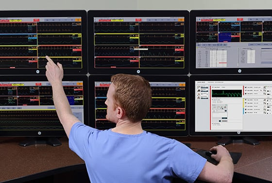A caregiver is working with multi monitoring screens to monitor telemetry data.