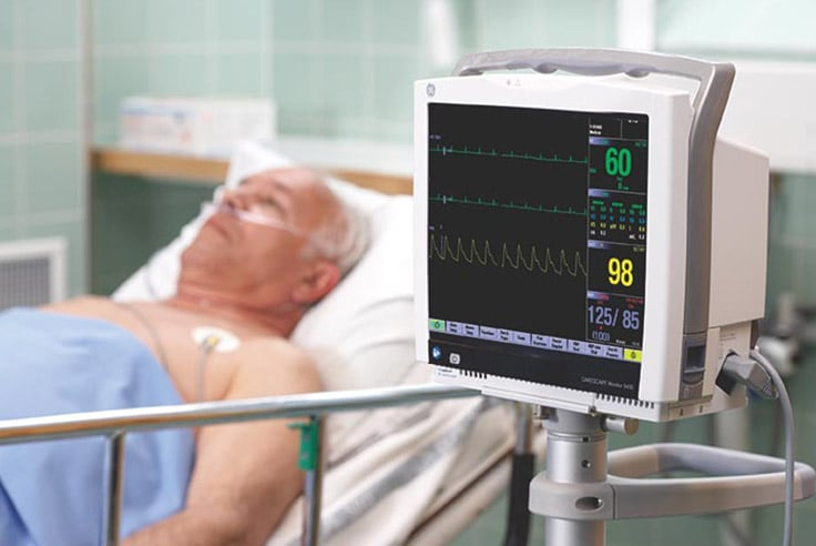 A caregivers uses GE Healthcare CARESCAPE B450 monitor to monitor patient data.