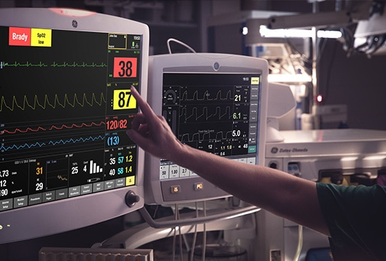 A caregivers is touching at the display screen of a GE Healthcare CARESCAPE B850 patient monitor to learn patient data.