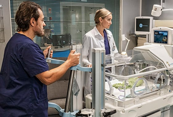 Two caregivers use GE Healthcare CARESCAPE B650 monitor to do patient monitoring for an infant in a hospital room.