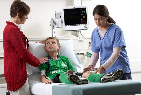 A young patient is being treated by a caregiver with help of GE Healthcare CARESCAPE B650 patient monitor.