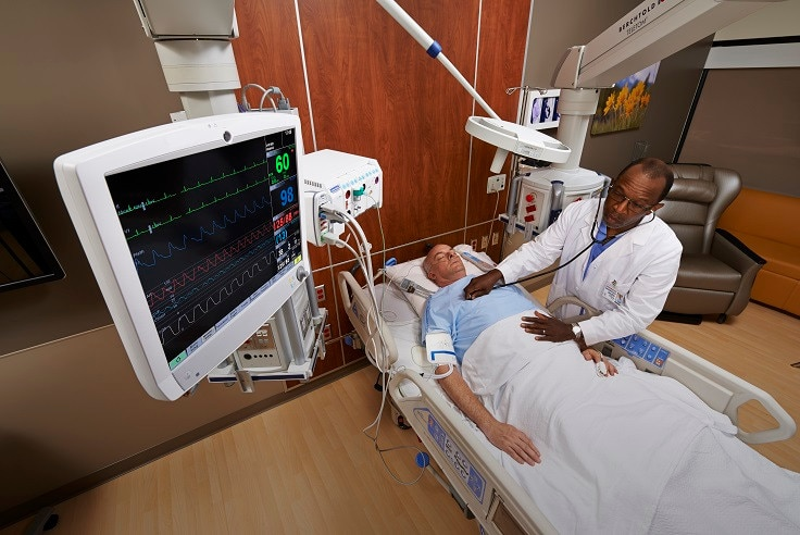 A caregivers is touching at the display screen of GE Healthcare CARESCAPE B850 patient monitor.