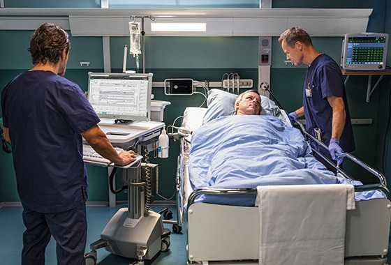 Two caregivers use GE Healthcare CARESCAPE B650 to monitor the patient's data.