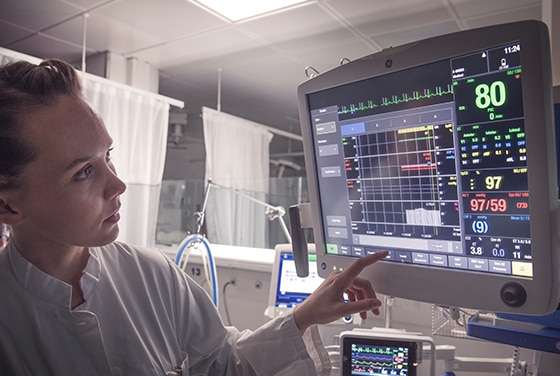 A caregiver is showing patient data on GE Healthcare patient monitors.