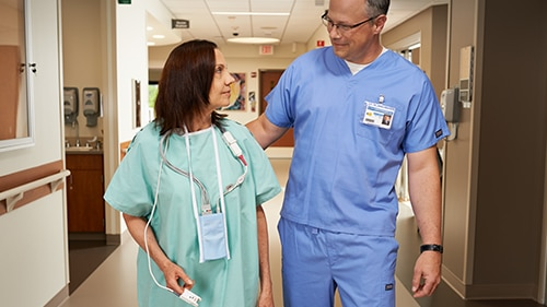 A patient and caregiver are walking in the hallway of a hospital.