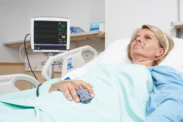 A patient is being monitored by GE Healthcare CARESCAPE monitoring platform.