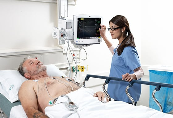 A caregiver uses GE Healthcare CARESCAPE B650 to monitor the patient's data.