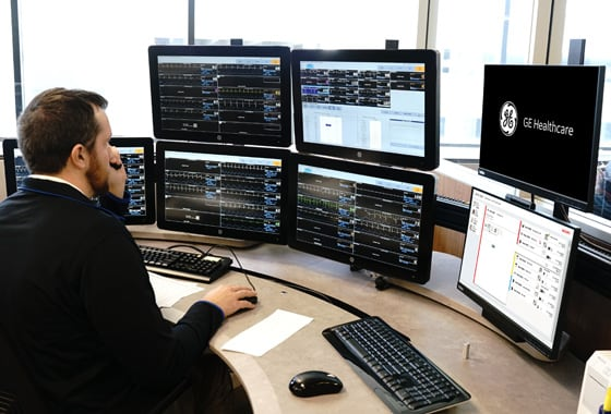 A technician is working with GE Healthcare Digital Centralized Monitoring Unit in a hospital room