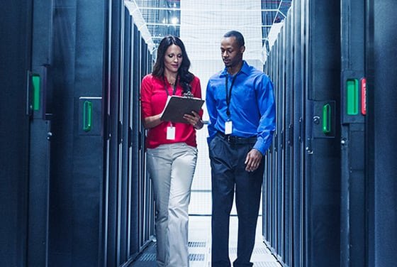 Two technicians are discussing CARESCAPE Network management while walking in a database equipment room.