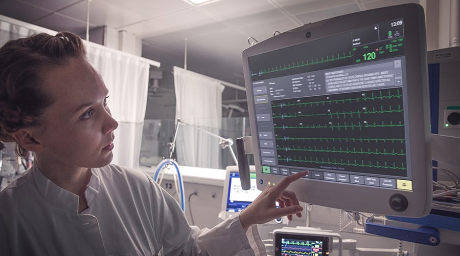 A caregiver is working on a GE Healthcare CARESCAPE™ ONE and monitoring patient data on screen.
