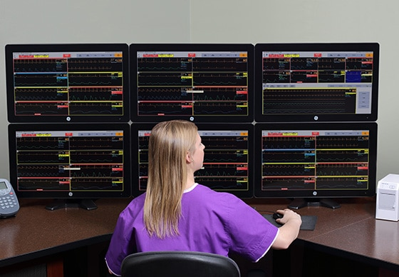 A caregiver is using the touch screen of a CARESCAPE Central Station to show data.