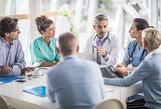 A care-team collaborate and discuss topics in a conference room.