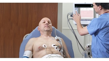 Monitoring a male patient with electrodes on him with a CARESCAPE Monitor B650